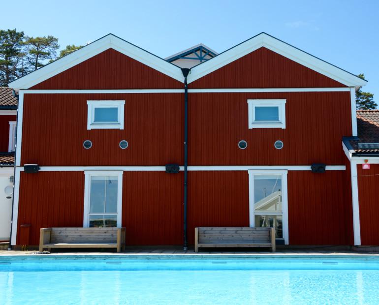 In Stockholms Schärengarten Sandhamn lädt ein rotes Holzhaus mit zwei Holzbänken vor einem Pool zum Verweilen ein.