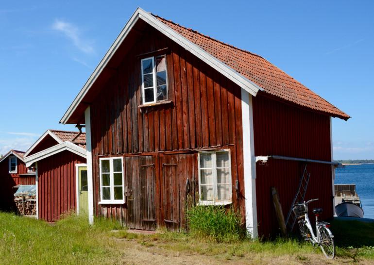 Aneinander gereihte und verwitterte rote Holzhäuschen bei Sandhamn dienten als Filmkulisse.
