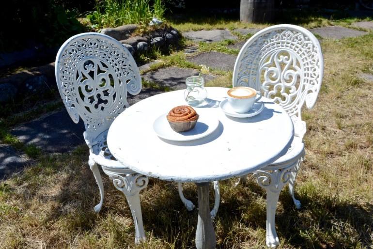 In einem Gartencafé in Stockholms Schärengarten Sandhamn ist an einer kleinen weißen Sitzgruppe ein Cappuccino und ein Zimtschnecke eingedeckt.