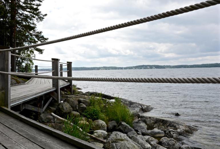 Ein Holzsteg nahe des Wassers führt in Stockholms Schärengarten Richtung Artipelag Värmdö.