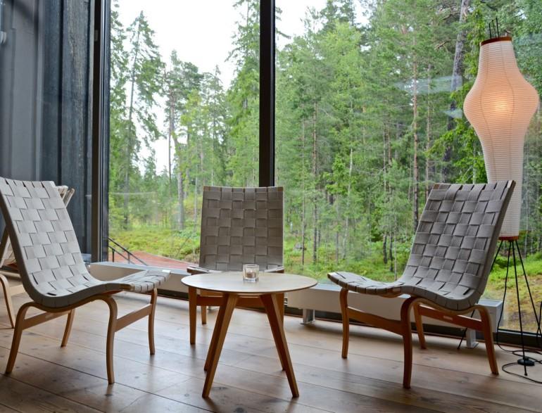 Eine kleine Sitzgruppe aus drei Stühlen und einem Tisch im Restaurant des Artipelag in Värmdö lädt zum Verweilen ein, an einer großen Fensterfront sieht man den Wald.