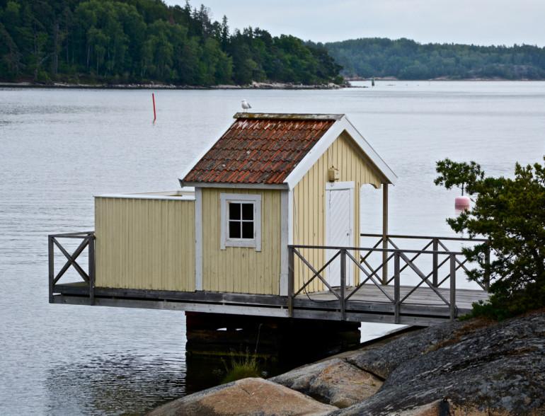 Auf einem Steg zur Ostsee steht ein kleines gelbes Badehäuschen.