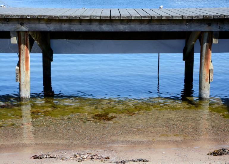 Ein Holzsteg ragt aus dem Wasser der Ostsee bei Sandhamn.