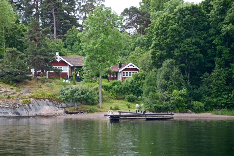 Zwei kleine Ferienhäuser mit roter Holzfassade stehen verdeckt von Bäumen am Seeufer von Stockholms Schärengarten.