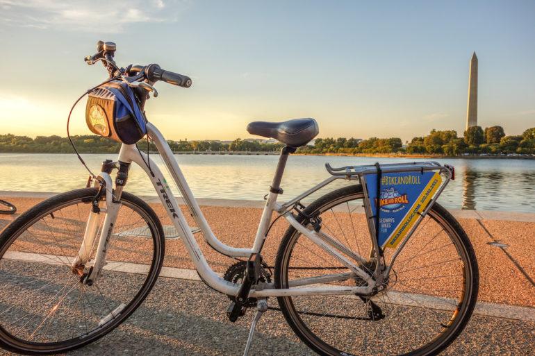 Ein weißes Leihfahrrad von Bike and Roll steht in Washington D. C., USA auf einer Straße, im Hintergrund ist das Washington Monument und Wasser bei Sonnenuntergang zu sehen.