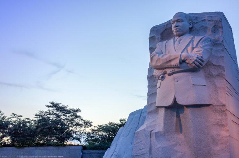 Bei Sonnenuntergang strotzt in riesiger Größe die aus Stein gemeisselte Statue von Martin Luther King mit festem Blick und verschränkten Armen in Washington D. C., USA.
