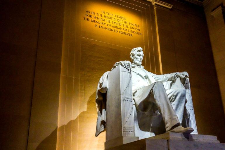 """In Washington D. C., USA thront Abraham Lincoln in weißem Stein gefasst auf einem Thron aus Büchern über ihm ist der Spruch: """"IN THIS TEMPLE AS IN THE HEARTS OF THE PEOPLE FOR WHOM HE SAVED THE UNION THE MEMORY OF ABRAHAM LINCOLN IS ENSHRINED FOREVER"""" beleuchtet."""
