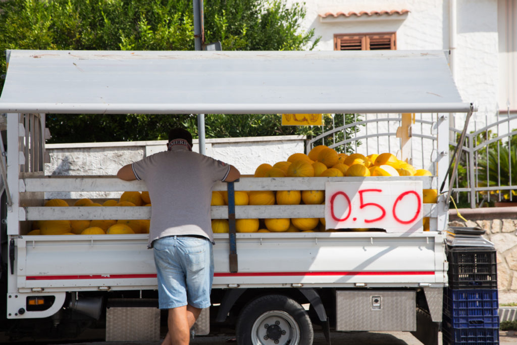 Auf einem Streetfood stand in Vieste werden Honigmelonen für 50 Cent verkauft: So stärkt ihr euch für euren Apulien Roadtrip.