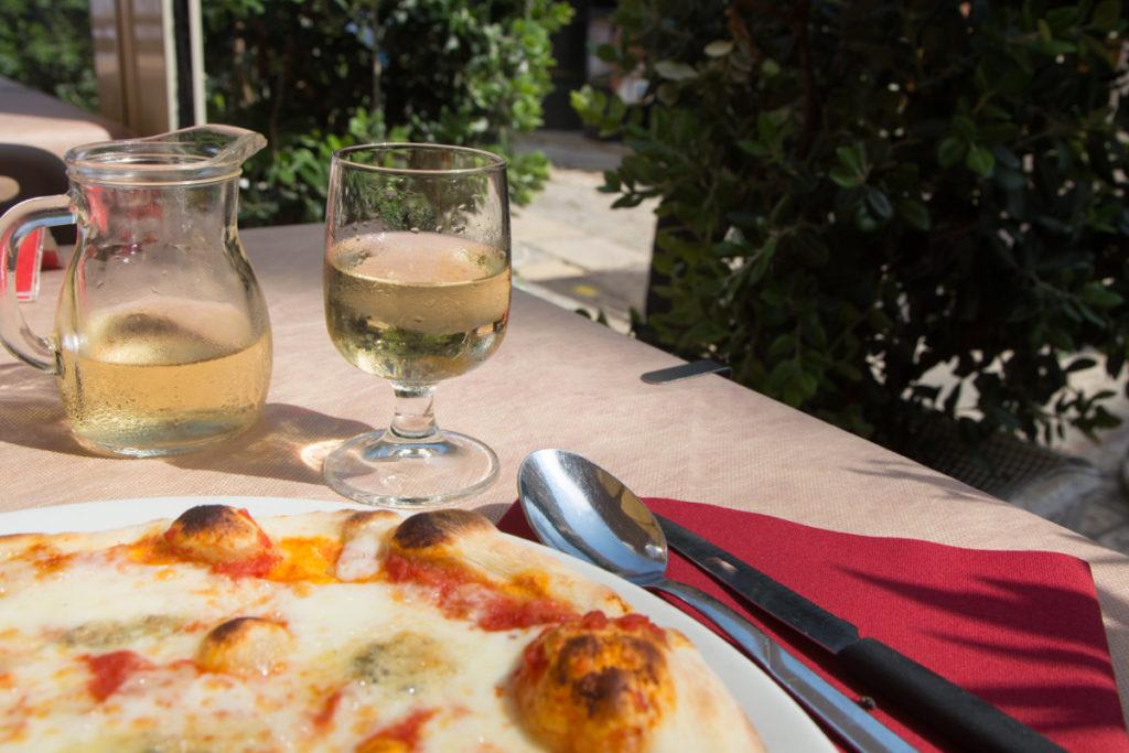 In einem Restaurant in Vieste, Apulien werden Pizza und Weißwein serviert.