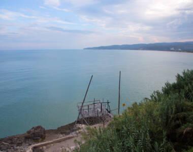 Die Meeresoberfläche glitzert, am Ufer befindet sich ein Fischergalgen - ein Highlight auf der Rundreise durch Apulien.