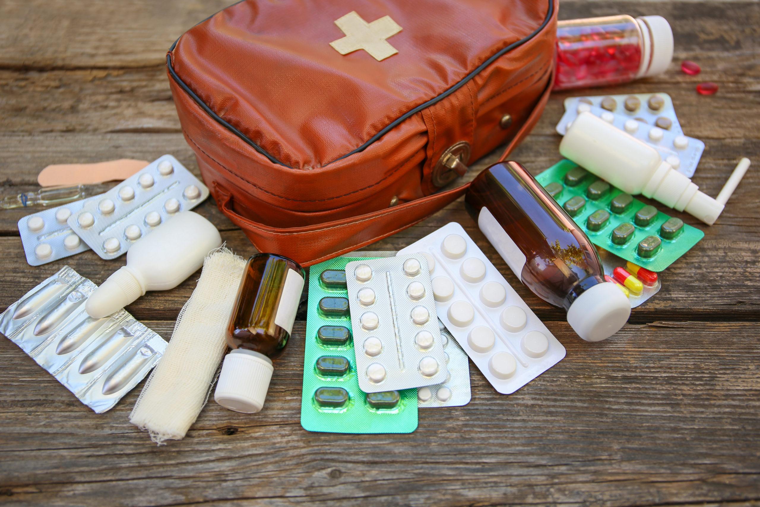 Eine Reiseapotheke in Form einer Erste-Hilfe-Tasche liegt auf Holz, davor liegen Tabletten, Zäpfchen, Medikamentenflaschen und Verbandszeug.