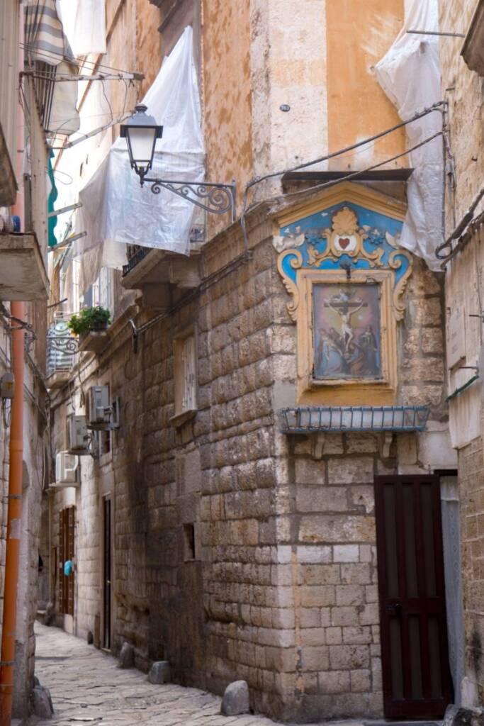 In einer Gasse in Apuliens Bari sind christliche Gemälde in eine Gebäudemauer gehauen.