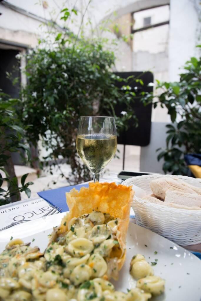 In einem Restaurant in Ostuni ist Weißwein und Orecchiette in einer Tapas Schüssel angerichtet.