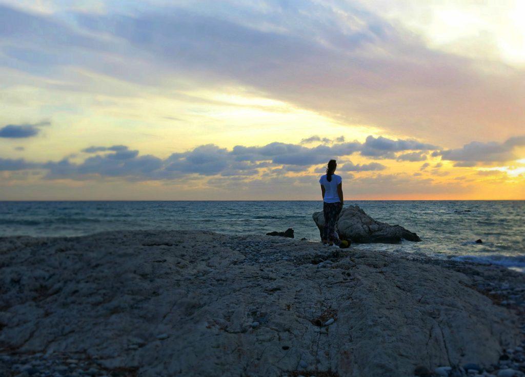 Reisebloggerin Eva genießt am Aphrodite-Strand Petra tou Romiou in Zypern den Sonnenuntergang über dem Meer.