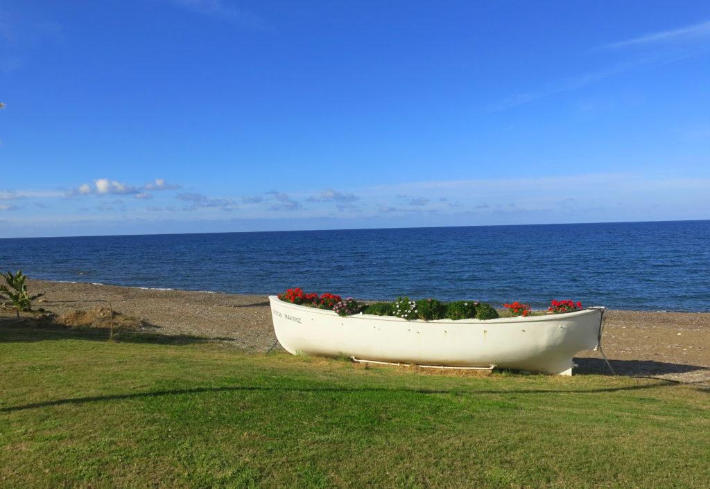 Den Strand bei Latsi in der Nähe von Paphos auf Zypern schmückt ein altes blumengeschmücktes Boot.