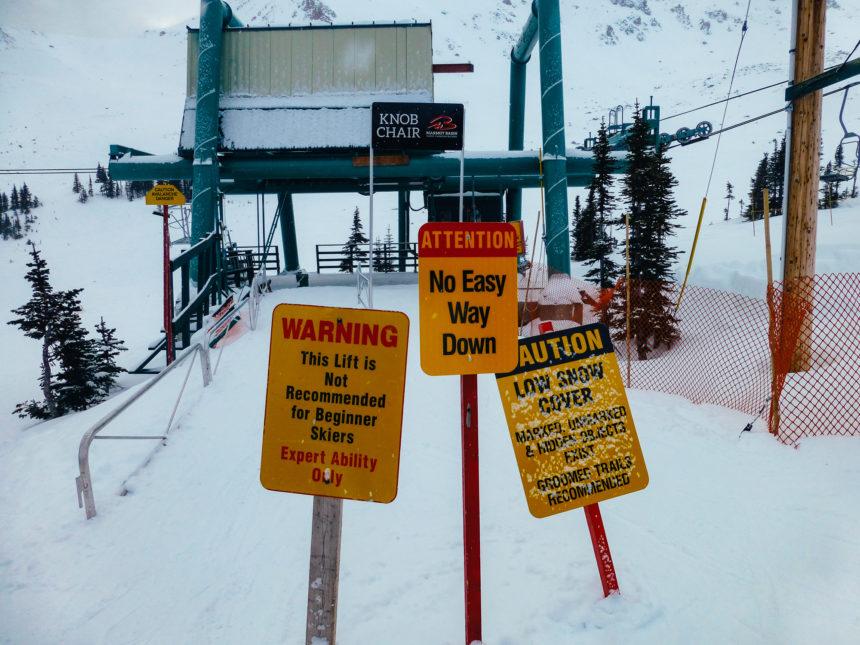 Gelbe Warnschilder auf einer kanadischen Skipiste warnen Skianfänger vor der schwierigen Abfahrt.