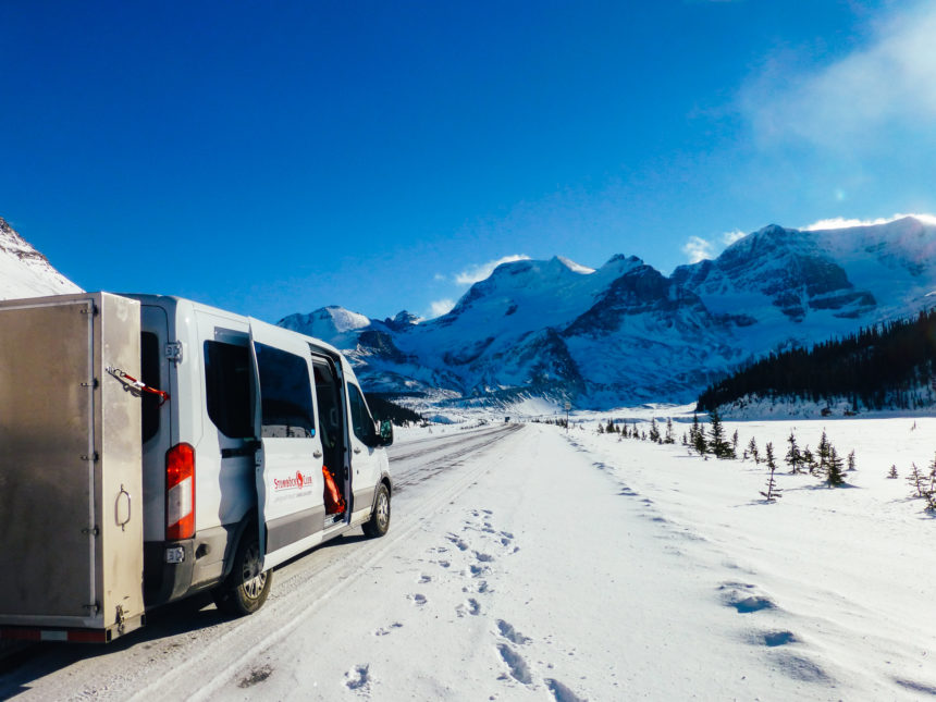 In Kanada nähe Lake Louise steht auf einer schneebedeckten Straße, bei wolkenlosem Himmel und eingeschneiter Bergkulisse ein weißer Transporter und hat die Schiebetür geöffnet.
