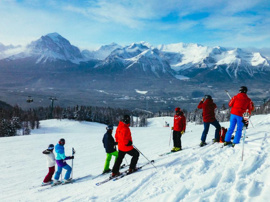 Eine Gruppe Skifahrer steht an einem Hang und blickt auf das kanadische, schneebedeckte Bergpanorama.