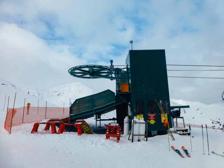 Ein grüner in die Jahre gekommener Skilift steht auf einer Piste in den Rocky Mountains.