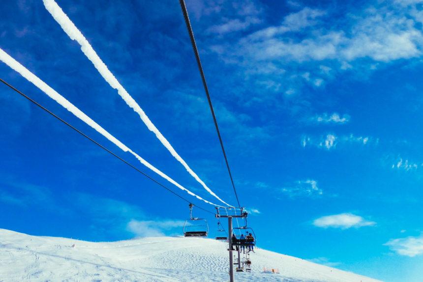 Unter strahlend blauem Himmel fährt ein Sesselift entlang einer kanadischen Skipiste.