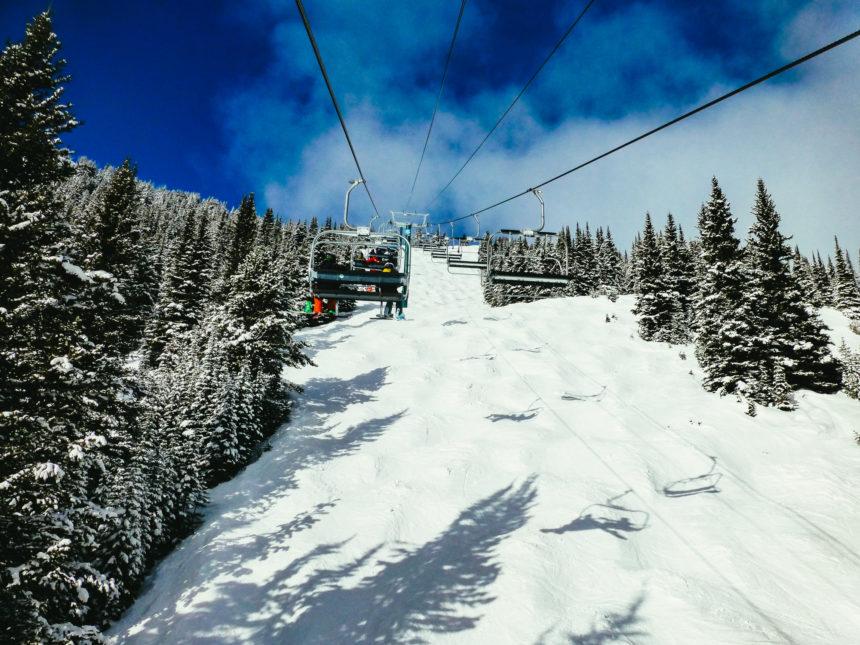 Ein Sessellift in Kanada fährt bei strahlend blauem Himmel die Skifahrer den schneebedeckten Hang hinauf.