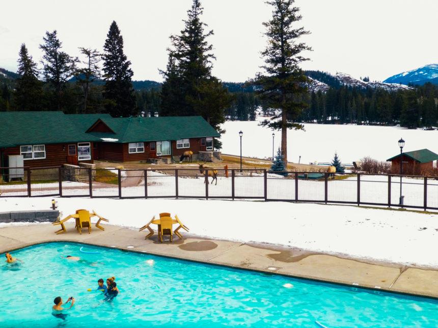 Inmitten der kanadischen Winter-Berglandschaft schwimmt eine Familie in einem Außenpool.