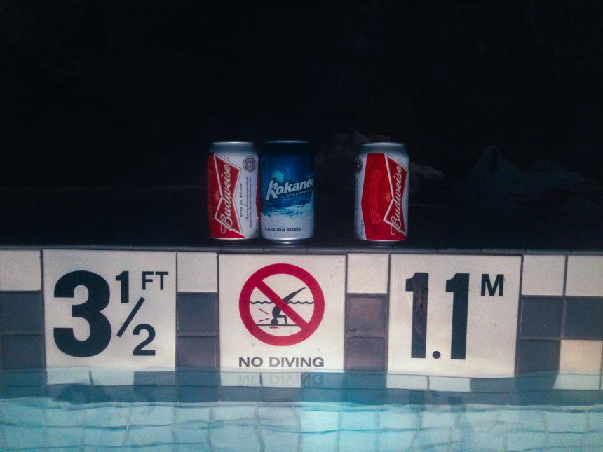 Drei Getränkedosen stehen am Rand eines Pools und seinen Hinweisschildern.