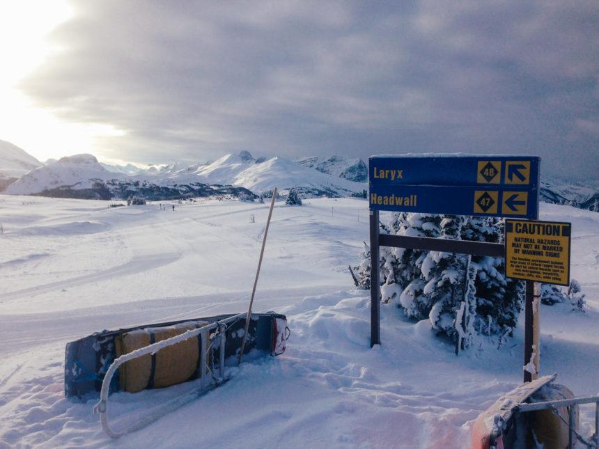 Die Sonne geht über der schneebedeckten Pistenlandschaft von Sunshine Village auf, ein gekippter Akia liegt neben einem blauen Wegweiser.