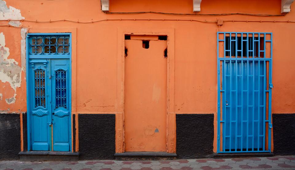 Auf den Kapverden in Sao Vicente Mindelo sind die Fassaden der Häuser in bunten und kräftigen Farben getaucht, auf diesem Bild umrahmt die knallig orange Wand zwei blaue Türen.