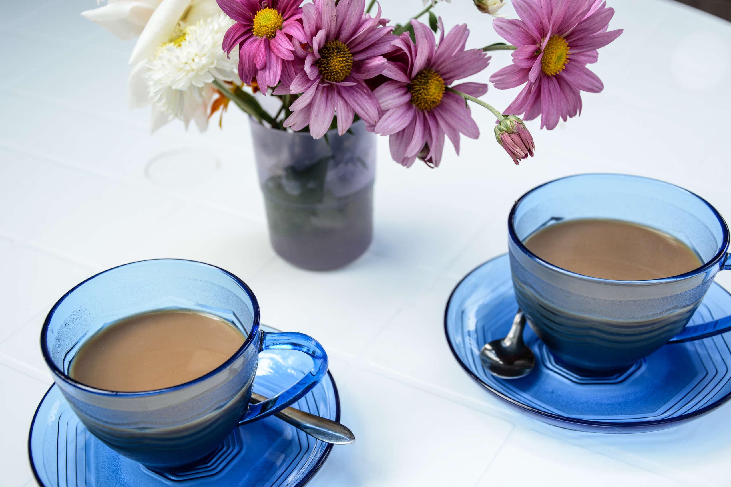 Zwei Kaffeetassen auf einem Tisch, dahinter Blumen in der Vase.