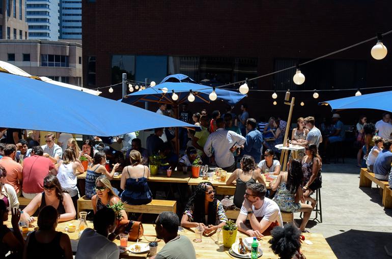 Unter blauen Sonnenschirmen des Neighbourgoods Market sitzen junge Menschen an Holztischen und essen, trinken und unterhalten sich.