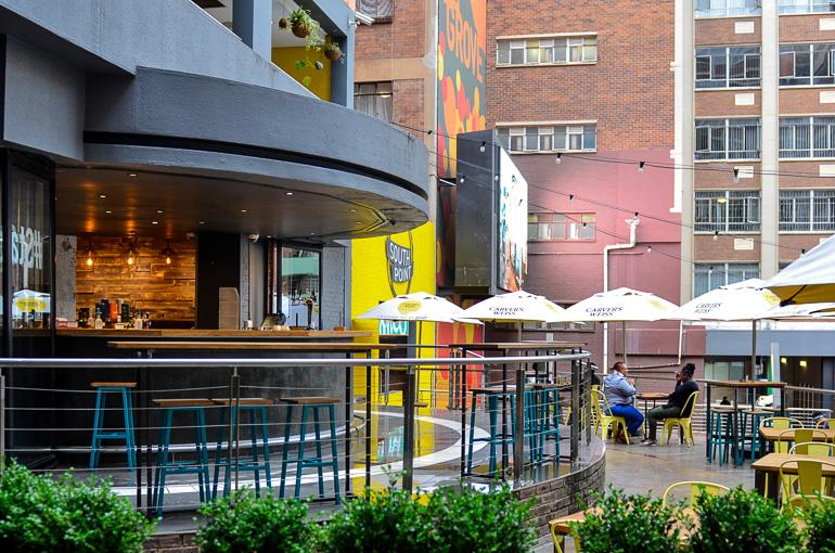 Zwei Gäste haben sich in der Außenbar im Once in Cape Town unter einem Schirm zum Verweilen eingefunden.