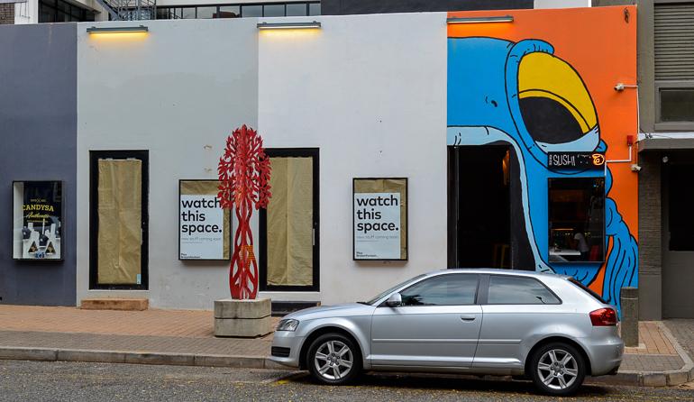 Ein silbernes Auto steht in Johannesburg vor einem Sushi-Restaurant dessen Eingang und Hauswand mit einem riesigen Fischmaul bemalt wurde.