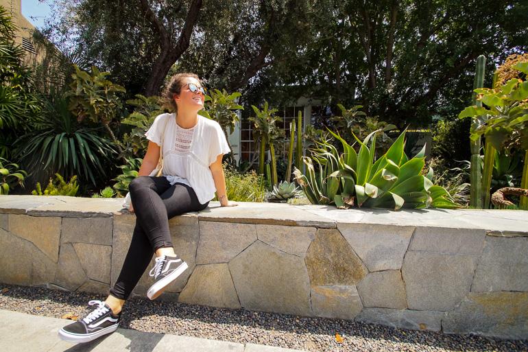 Auf einem kleinen Mauervorsprung bei Melrose Place in Los Angeles genießt eine Frau den Blick in die Sonne, hinter ihr blühen Kakteen.