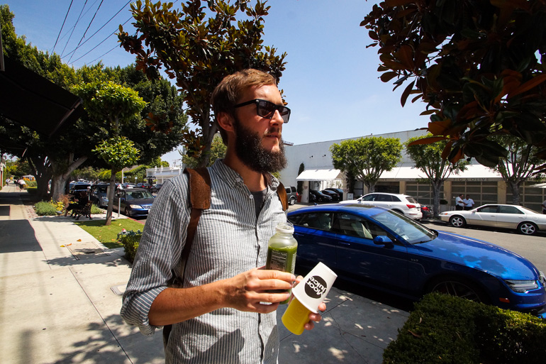 Ein Mann läuft durch die Straßen von Los Angeles und hält in beiden Händen gesunde und vitaminreiche Säfte.