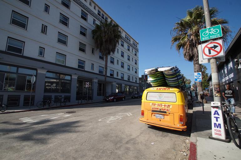 Ein gelber Bus in Los Angeles mit Surfbrettern auf dem Dach.