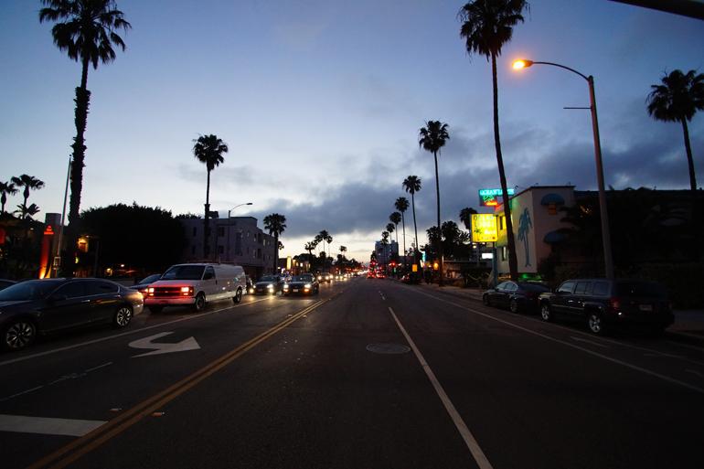 Eine Straße am Abend mit Palmen an den Seiten.