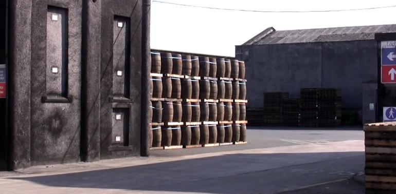 Im Innenhof der Destillerie Loch Lomond in Schottland sind viele Whisky Fässer gelagert.
