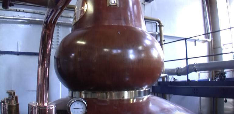 Die bräunliche Brennblase der Whiskybrennerei Deanston Stills in Schottland hat am Bauch eine kleine Taille mit einem Metallgürtel.