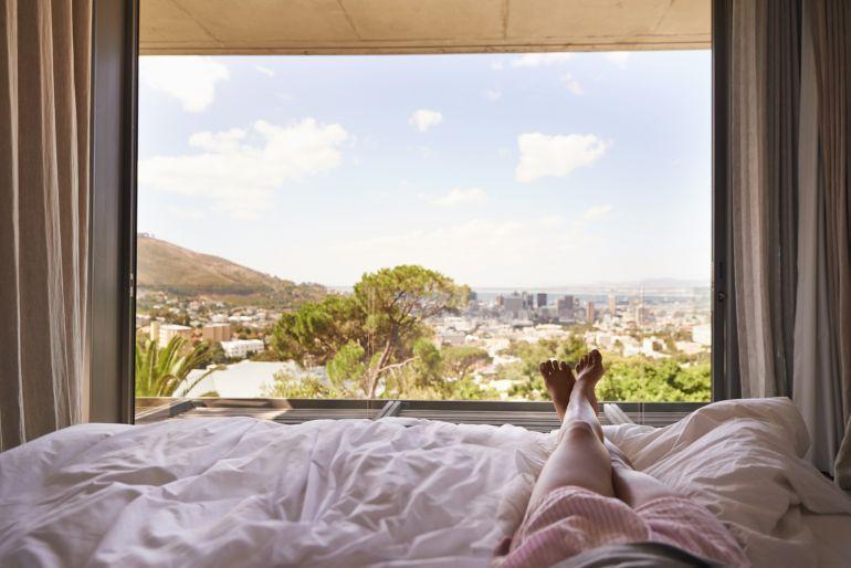 Frau liegt im Bett und betrachtet die vor ihr liegende Aussicht auf die Natur.