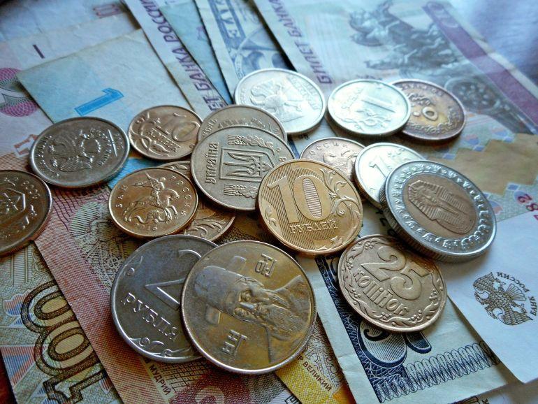 Blick auf Geldscheine und Münzen unterschiedlicher Währungen