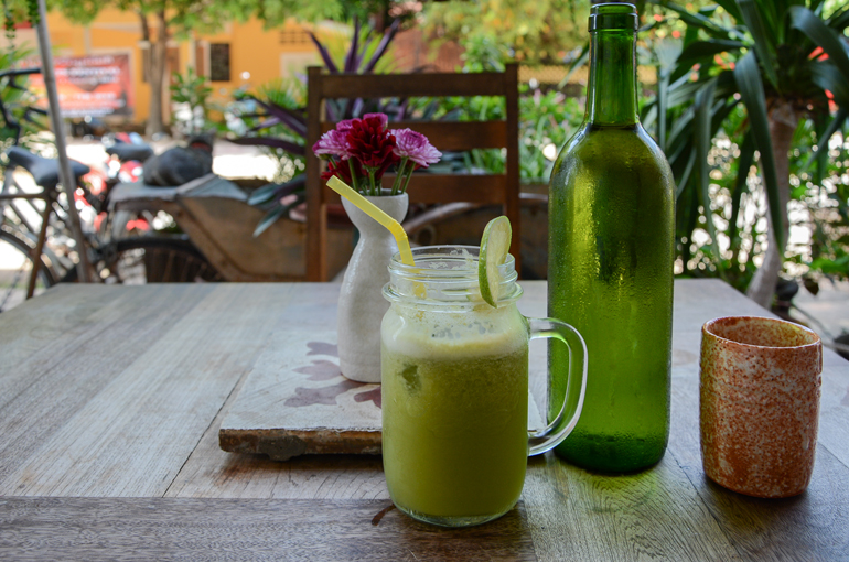Ein grüner Smoothie steht in einem Cafe in Kampot bei Kambodscha auf einem Tisch.