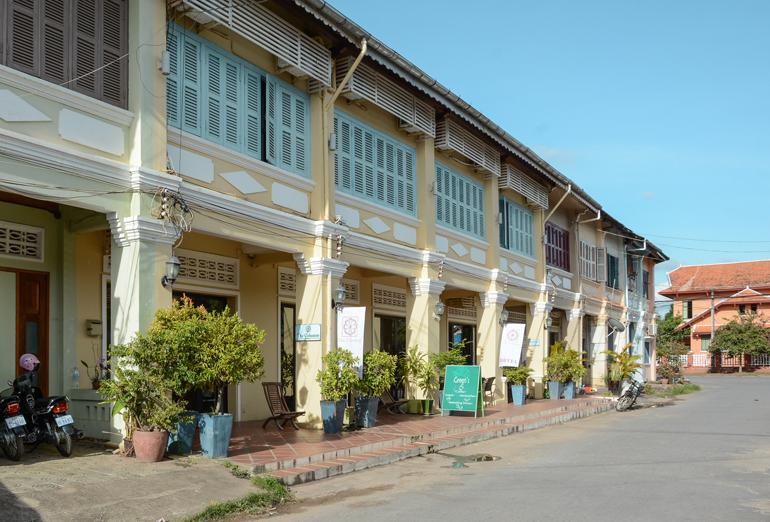 An den Arkaden der Häuser von Kampot stehen Sonnenschirme und Pflanzen davor.
