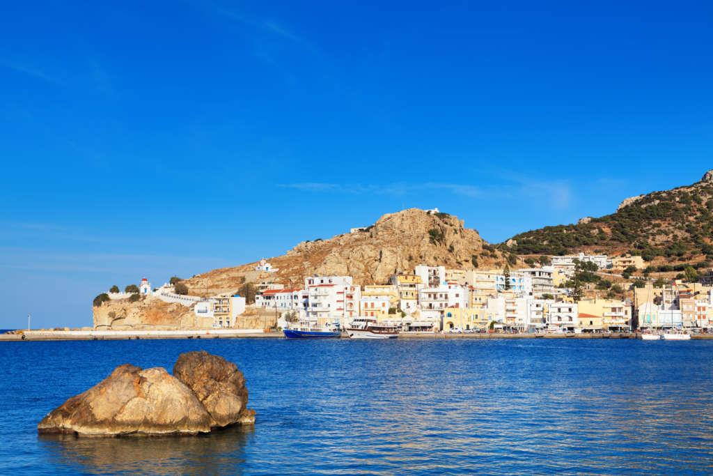 Vom Strand Pigadia aus genießt man den Blick über das Meer auf die am Felsen liegende Stadt Pigadia auf Karpathos.
