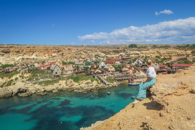 Frau sitzt auf einem Felsvorsprung und blickt hinab auf das Popeye Village - eine Kulissenstadt mit bunten Holzhäusern