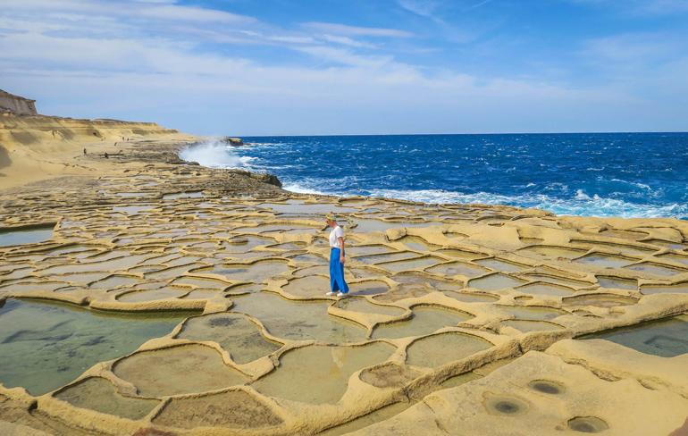 Frau läuft über die mit Meerwasser gefüllten Salzpfannen von Gozo