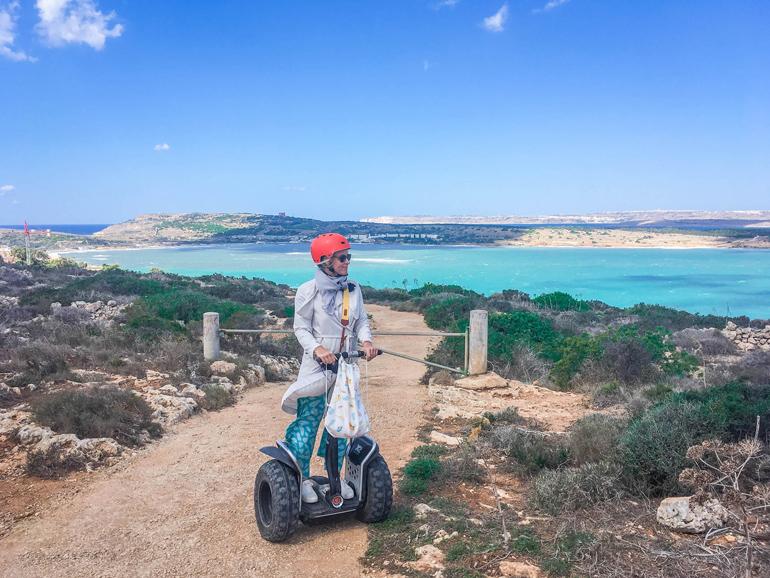Frau steht auf einem Segway an einem Aussichtspunkt in Selmun