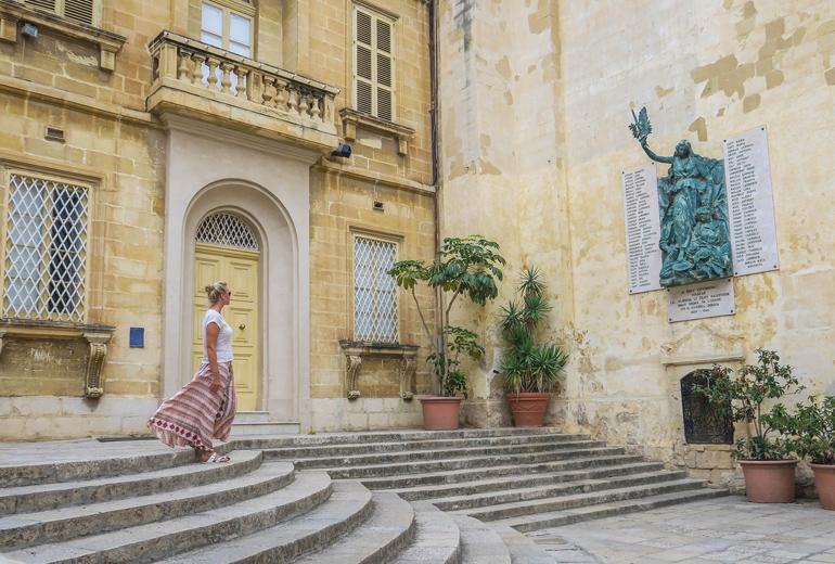 """Frau blickt auf Denkmal an Hauswand in Vittorosia, eine der """"Drei Städte"""""""