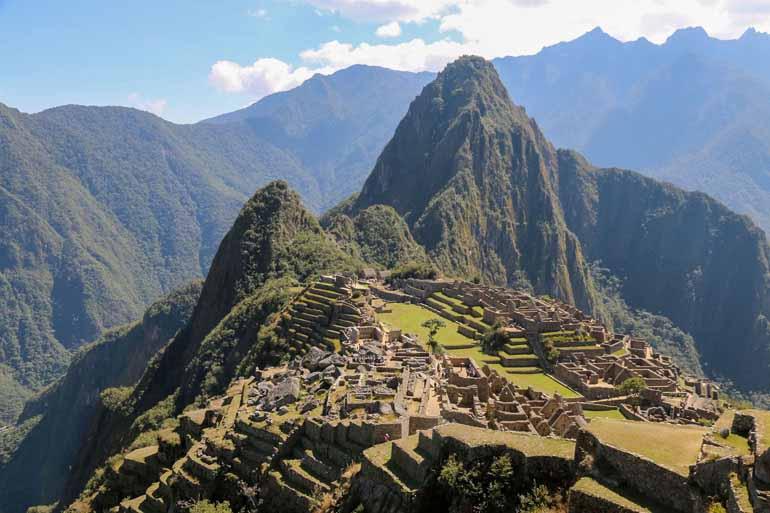 Ausblick auf den Machu Picchu mit Mauern im Vordergrund.
