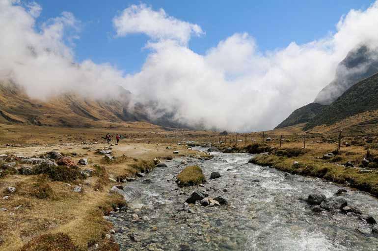 Fluss in einem Bergtal mit zwei Wanderern.